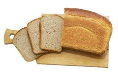 Barra de pan en un tablero de madera aislado en el fondo blanco imagenes de archivo