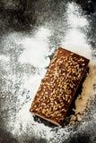 Barra de pan rústica con las semillas y la harina de girasol en la pizarra negra Imagen de archivo