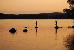 Barra de pesca de los niños en el lago en la puesta del sol Imágenes de archivo libres de regalías