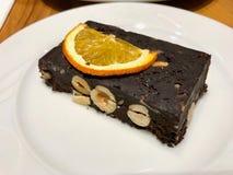 Barra de porca crua do chocolate sem farinha e e nenhum açúcar servido com fatia alaranjada secada fotos de stock