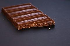 Barra del chocolate con leche con las avellanas machacadas y las pasas del alcohol aisladas en fondo negro Confitería dulce delic fotografía de archivo