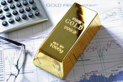 Barra della verga d'oro su un diagramma dei valori di borsa Fotografie Stock