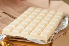 Barra di cioccolata bianca sulla base dell'oro Fotografia Stock Libera da Diritti