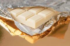 Barra di cioccolata bianca sulla base dell'oro Fotografie Stock