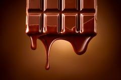 Barra di cioccolato con la sgocciolatura fusa del cioccolato fondente sopra il fondo marrone scuro Contesto di concetto della con fotografia stock