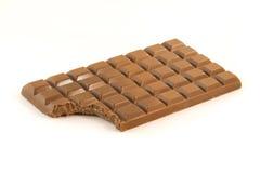 Barra di cioccolato con un morso mancante sopra bianco Fotografie Stock