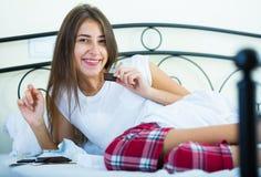 Barra di cioccolato godente castana adolescente a letto Fotografia Stock Libera da Diritti