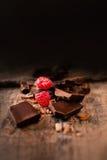 Barra di cioccolato rotta con i lamponi maturi rossi su marrone scuro b Immagini Stock