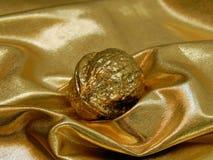 Barra di oro con un dado dalla foglia di oro su un fondo dell'oro Fotografia Stock Libera da Diritti