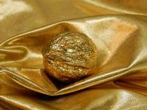 Barra di oro con un dado dalla foglia di oro su un fondo dell'oro Immagini Stock Libere da Diritti