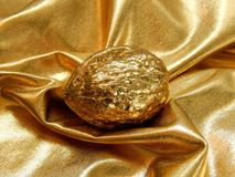 Barra di oro con un dado dalla foglia di oro su un fondo dell'oro Fotografia Stock