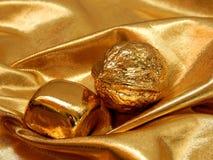 Barra di oro con un dado dalla foglia di oro su un fondo dell'oro Fotografie Stock Libere da Diritti