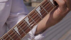 Barra do recolhimento das cordas de uma guitarra elétrica branca e da guitarra do metal que são filme