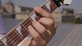 Barra do recolhimento das cordas de uma guitarra elétrica branca e da guitarra do metal que são video estoque