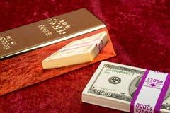 Barra e dinheiro de ouro Fotografia de Stock Royalty Free