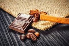 Barra e especiarias de chocolate na tabela de madeira fotografia de stock