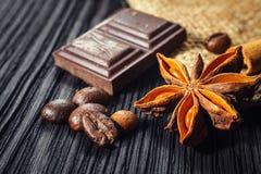 Barra e especiarias de chocolate na tabela de madeira imagens de stock