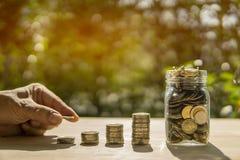 A barra e o frasco das moedas da mão do homem na tabela de madeira no fundo da luz solar e do borrão apresentam as economias inve foto de stock