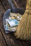 Barra el dinero con una escoba para recoger en la cucharada imagen de archivo libre de regalías