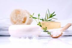 Barra herbaria del jabón del balneario en la toalla de baño blanca con el tomillo, romero y imagenes de archivo