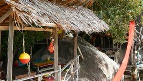 Barra relajante del reggae del rasta del cáñamo en la playa tropical del verano de ramas de madera Banderas de Rastafarian con ma metrajes
