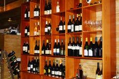 Barra y botellas de vinos en estantes Imagenes de archivo