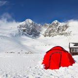 Barraca de escalada vermelha brilhante na neve fotos de stock