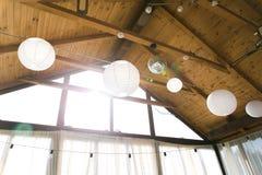 Barraca decorada com festão do bulbo O casamento setup lanternas do Livro Branco dentro da construção, sob a decoração de madeira imagem de stock