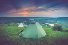 Barraca do turista no prado verde no por do sol Fundo de acampamento Imagem de Stock Royalty Free