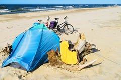 Barraca e bicicletas azuis no Sandy Beach abandonado selvagem Acampamento no turismo da bicicleta da costa de mar Báltico imagem de stock