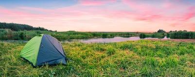 Barraca verde do turista no banco de rio no alvorecer Imagem de Stock