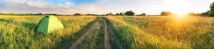 Barraca verde no campo perto da estrada no por do sol Foto de Stock Royalty Free