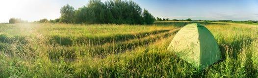 Barraca verde no campo verde perto da estrada no por do sol Imagem de Stock Royalty Free