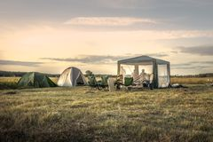 Barracas de acampamento do local de acampamento no céu do por do sol do campo do verão durante feriados de acampamento fotografia de stock royalty free