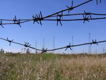 Barrage hard barbed wire on the background of the restricted area in the radio tower field stock images