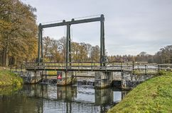Barrage in a little river. Small concrete barrage with a pedestrian bridge across the Berkel river near Zutphen, The Netherlands on an afternoon in the beginning stock photography