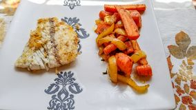 Barramundi fish, pan fried, next to side of grilled onions and carrots stock images