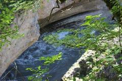 Barranco con un río de la montaña Visión a través de ramas de árbol foto de archivo
