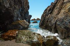 Barranco de la roca de la playa del día soleado foto de archivo libre de regalías