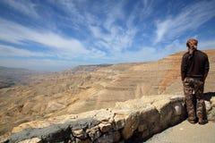 BARRANCO MUJIB, JORDÂNIA - 6 DE MARÇO DE 2016: Um homem jordano novo que olha Wadi Mujib Canyon dos reis Estrada fotos de stock royalty free