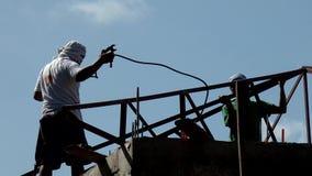 Barras de ángulo de la soldadura del trabajador para hacer los bragueros del tejado siluetas almacen de video