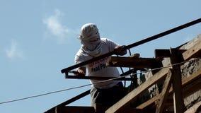 Barras de ángulo de la soldadura del trabajador para hacer los bragueros del tejado siluetas almacen de metraje de vídeo