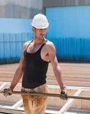 Barras de acero que llevan del trabajador de construcción Fotos de archivo