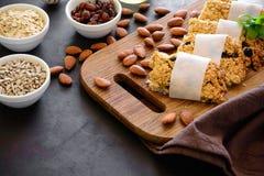 Barras de café da manhã super do alimento com aveia, sésamo, sementes de girassol, mel e porcas no fundo de madeira marrom imagens de stock royalty free