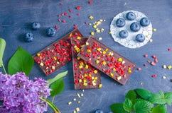 Barras de chocolate con el melocotón y las fresas secados imagen de archivo