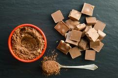 Barras de chocolate con el montón del polvo de cacao Imagenes de archivo