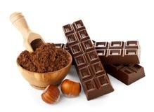 Barras de chocolate con el polvo de cacao aislado en blanco Imágenes de archivo libres de regalías