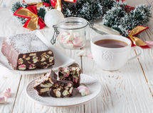 Barras de chocolate con las melcochas y las galletas en una tabla de madera blanca Año Nuevo e invitación de la Navidad Foto de archivo