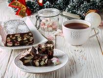 Barras de chocolate con las melcochas y las galletas en una tabla de madera blanca Año Nuevo e invitación de la Navidad Fotos de archivo libres de regalías
