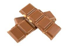 Barras de chocolate do leite com as avelã isoladas em um fundo branco Imagem de Stock